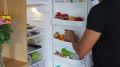 Breaking the diet - hungry man goes to the fridge to snack on some cake - stock footage