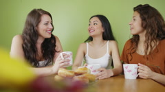 Female friends gossiping together with coffee and cakes - stock footage