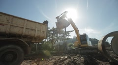 City ​​works. excavator placing land into truck in sunny day. Medium shot. Stock Footage
