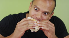 Stock Video Footage of Man with big appetite eating a hamburger with great enjoyment