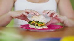 Woman with big appetite eating a hamburger with great enjoyment Stock Footage
