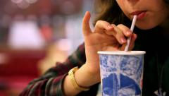 Fast food restaurant : girl drinking cold beverage with straw Stock Footage