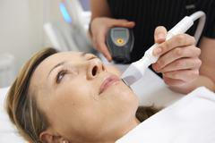 beautician carrying out ultrasound skin rejuvenation treatment - stock photo