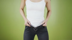 Time to go on a diet - woman struggling to get into too tight jeans - stock footage