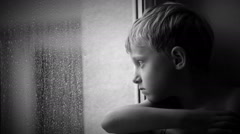 Alone little boy looks raindrops through window glass Stock Footage