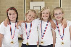 Female school sports team in gym with medals Stock Photos