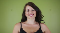 Portrait of happy attractive woman standing against green background - stock footage
