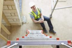 construction worker falling off ladder and injuring leg - stock photo