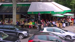 A classic Paris outdoor cafe with many patrons and waiters serving. Stock Footage