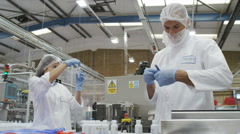 Workers in protective clothing in pharmaceutical and cosmetics factory - stock footage