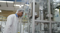 Asian man inspecting products and machinery pharmaceutical and cosmetics factory Stock Footage