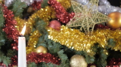 Fading from the wind Christmas candle amidst an elegant Christmas tree. - stock footage