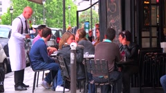 A waiter serves customers at a typical Paris sidewalk cafe. Stock Footage