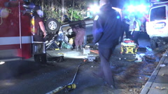 Flipped car accident night wide shot zoomin Stock Footage