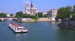 A riverboat travels on the Seine near the Notre Dame cathedral in Paris. Stock Footage