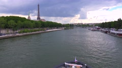A bateaux mouche riverboat passes under the camera near the Eiffel Tower. Stock Footage