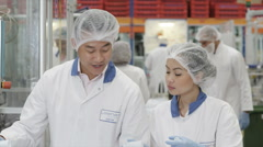 Asian workers on a production line in pharmaceutical and cosmetics factory - stock footage