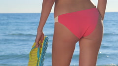 Girl in pink bikini with flip flops at the summer beach Stock Footage