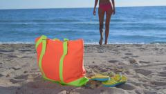 Colorful bag and flip-flops on sandy beach bikini woman in background Stock Footage