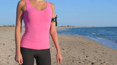 Fitness girl with phone in arm sport band exercising on the beach Stock Footage