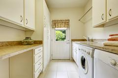 Bright laundry room with white cabinets Stock Photos