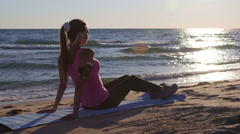 Fitness sporty woman relaxing after workout on beach at sunset Stock Footage