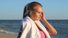 Face of fitness girl relax listening to music after workout on the beach Stock Footage