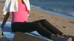 Fitness girl relaxing after workout on the beach Stock Footage