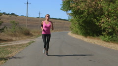 Fitness running woman jogging during outdoor workout along country road Stock Footage