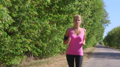 Fitness athletic girl jogging along the road during outdoor workout Stock Footage
