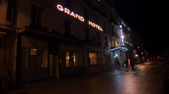 A neon sign announced the Grand Hotel in a rainy French city. - stock footage
