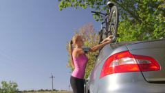 Sporty young woman takes down bicycle from roof of his car Stock Footage