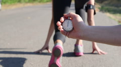 Stopwatch in hand  female runner athlete feet running on road Stock Footage