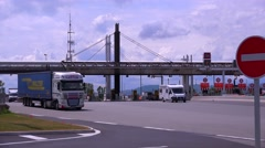 Trucks and cars pass through a tollbooth on a French motorway. Stock Footage