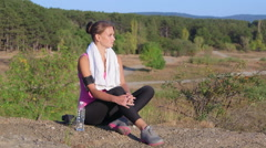 Fitness young woman relaxing after workout exercise on nature Stock Footage