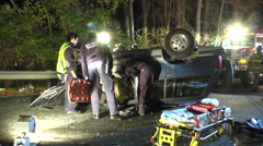 Overturned car night first responders on scene Stock Footage