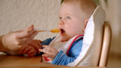 Mother feeding baby boy with spoon 4/6 Stock Footage
