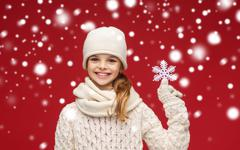smiling girl in winter clothes with big snowflake - stock illustration