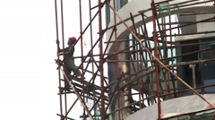 Chinese building worker handles a scaffolding pipe on tall building Stock Footage