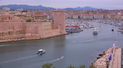 Boats enter and exit the harbor in Marseilles, France. - stock footage