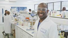 Portrait of black male scientist with science team in lab Stock Footage