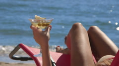 Female hand holding martini cocktail with olives on tropical beach Stock Footage