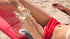 Young woman holding martini cocktail with olives on summer beach - stock footage