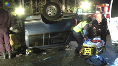 Overturned car night first responders save driver Stock Footage