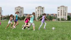 Children playing football. Kids playing soccer. Girls running for boy with ball. - stock footage