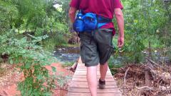 Man Crossing Foot Bridge Over Oak Creek- Red Rock State Park Stock Footage