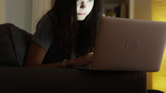 Mixed race woman using laptop at night Stock Footage