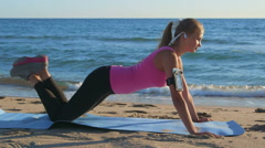 Fitness routine for women - athletic girl doing push-ups on beach Stock Footage