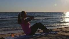 Fitness routine for women - athletic girl doing abdominal crunch on the beach - stock footage