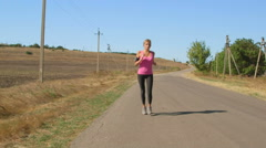 Young female athlete runner jogging during outdoor workout - stock footage